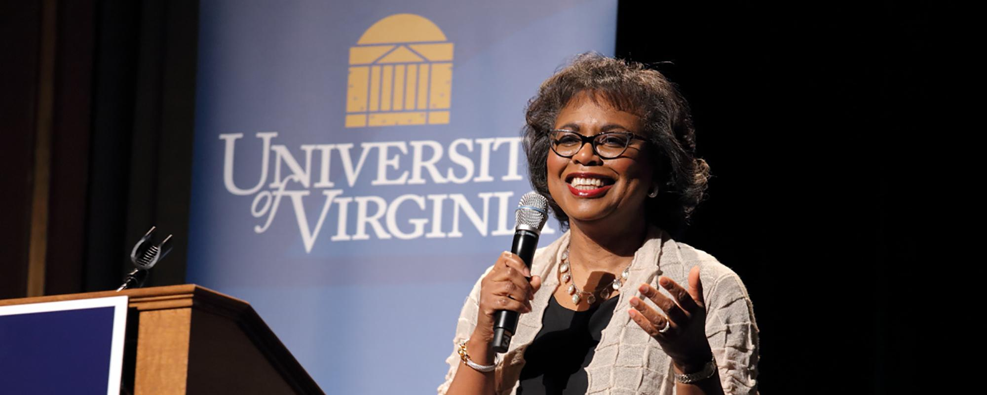 Anita Hill stands next to podium smiling and holding a microphone, gesturing with her left hand.