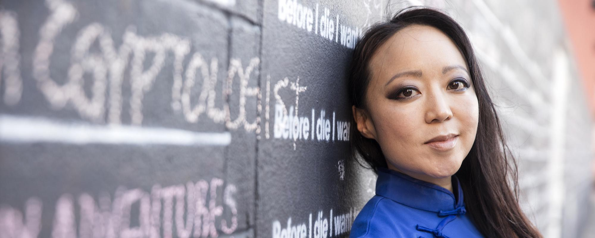 "portrait of Candy Chang against ""Before I Die"" wall"