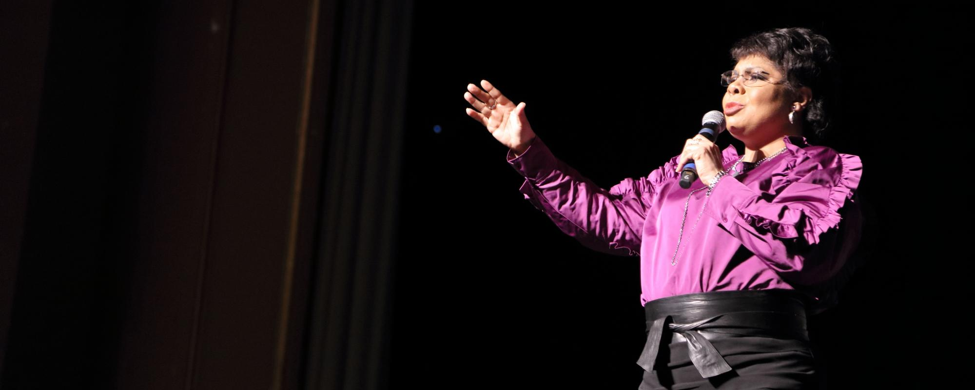 April Ryan wearing purple blouse, holding microphone and gesturing with right hand.